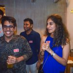 laughing team members wearing tags and enjoying beer while playing games